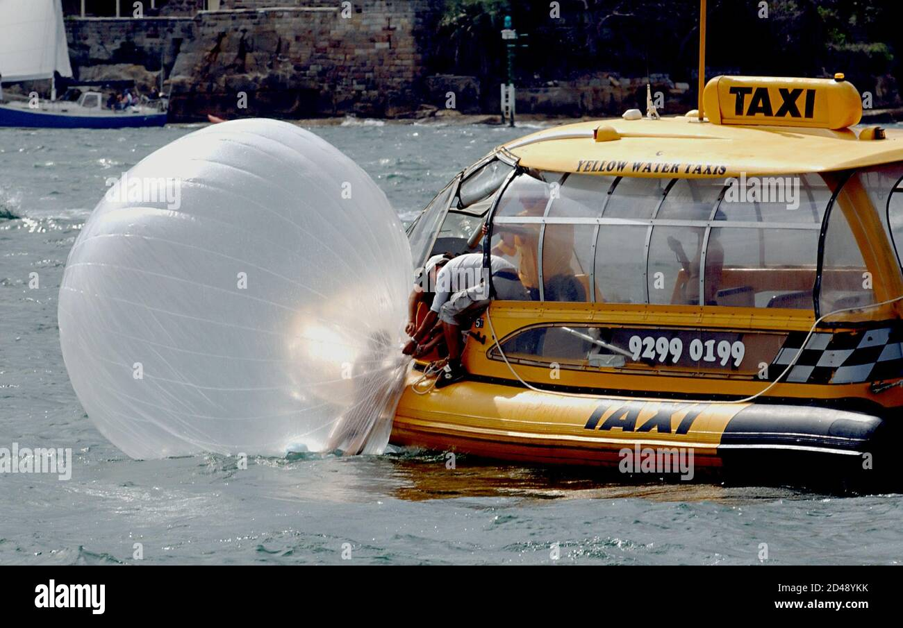 Beijing performance artist Zhu Ming climbs onto a water taxi on Sydney Harbour March 9, 2003 after he took to the water inside his plastic bubble. Part of a new generation of Chinese performance artists, Ming is in Sydney as part of the Musuem of Contemporary Art's Liquid Sea exhibition. The bubble is four metres in diameter and requires 33 cubic metres of compressed air, allowing a maximum performance of under an hour. Ming, an experienced swimmer, carries a small blade to cut himself free in an emergency. REUTERS/James Morgan  JDM/FA Stock Photo