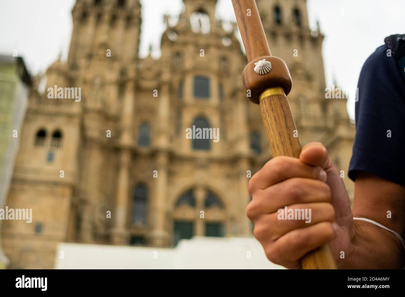 closeup of pilgrim hand holding walking stick with scallop shell, symbol of the camino de santiago pilgrimage, in front of the santiago cathedral Stock Photo