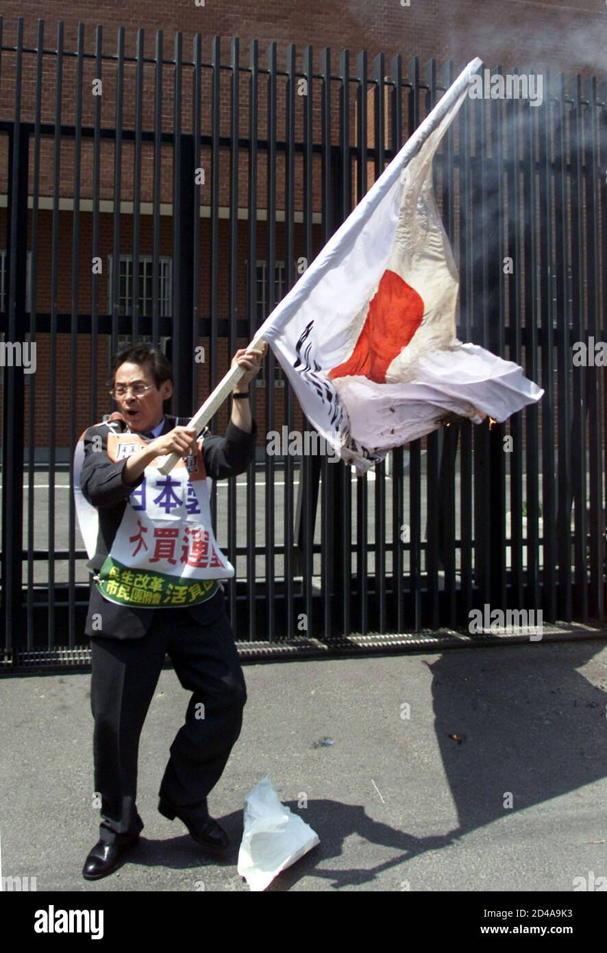 "HOLDING A BURNING JAPANESE NATIONAL FLAG, A SOUTH KOREAN PROTESTER SHOUTS SLOGANS IN FRONT OF JAPANESE EMBASSY IN SEOUL.   Holding a burning Japanese national flag, South Korean protester Hong Jeong-sik shouts anti-Japan slogans in front of the Japanese Embassy in Seoul May 14, 2001. Hong was protesting against controversial middle school history text book of Japan, which critics say justifies Japan's wartime atrocities. The characters on his chest reads, ""Civic campaign to boycott Japanese products"". Stock Photo"
