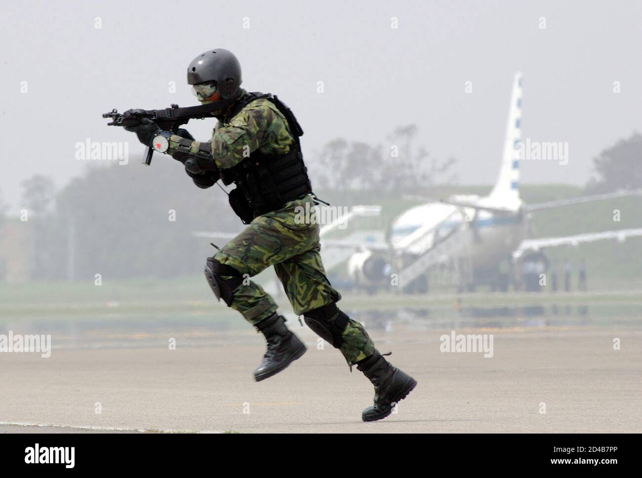 """Taiwanese soldier from special forces division takes part in anti-airborne drill at CCK air base in central city of Taiwan.  A Taiwanese soldier from the special forces division takes part in an anti-airborne drill at the CCK air base, in the central city of Taiwan, July 27, 2005. The military exercise, involving simulated repulsion of airborne assaults on an airbase, are part of Taiwan's annual """"Han Kuang"""", or Chinese Glory, exercises aimed at testing the military's readiness against a Chinese invasion. Taiwan President Chen Shui-bian warned on Tuesday that arch-rival China's growing missile  Stock Photo"""