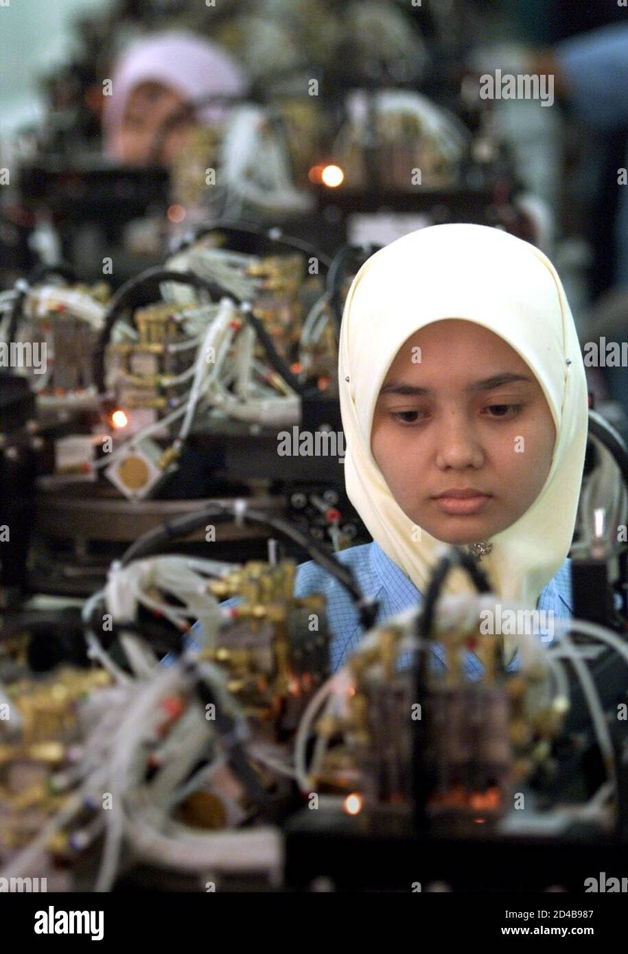 """Malaysian Noorrehan Ishak works at an electronics factory in Malaysia's western state of Penang, April 19, 2001. Electronics industry workers in Penang, also known as """"Silicon Island"""", are watching their backs but so far the tropical technology hub has escaped the worst of a global round of high-tech sackings. Picture taken on April 19, 2001.  BM/CC Stock Photo"""