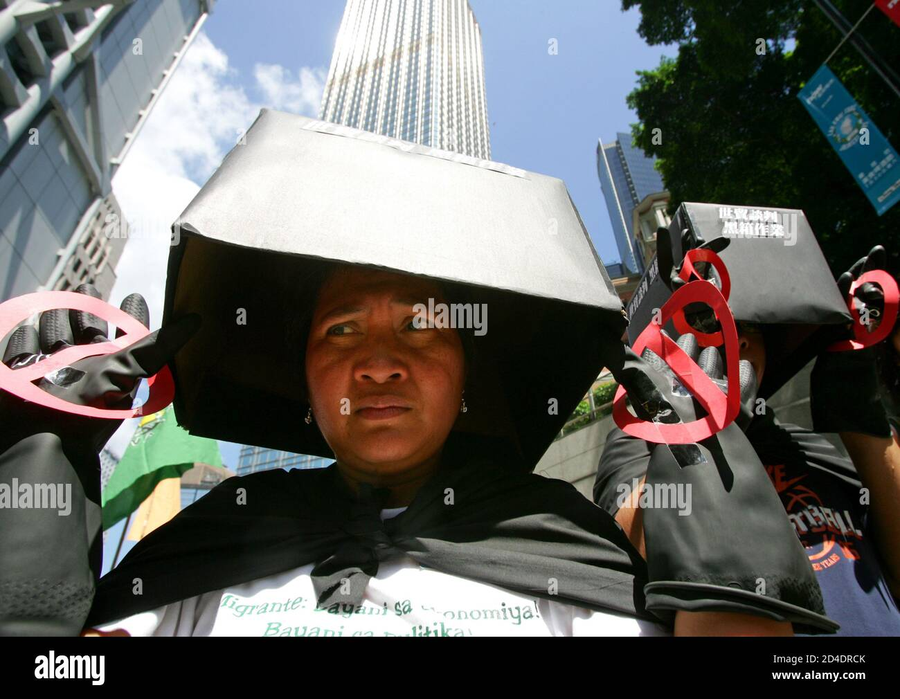 """A protester, with a black box covering her head to symbolise the government leaving the people in the dark during the negotiation on the """"General Agreement on Trade in Services"""" (GATS), takes part in an anti-WTO march held by the Hong Kong People's Alliance on WTO in Hong Kong July 24, 2005. REUTERS/Paul Yeung  PY/CCK Stock Photo"""