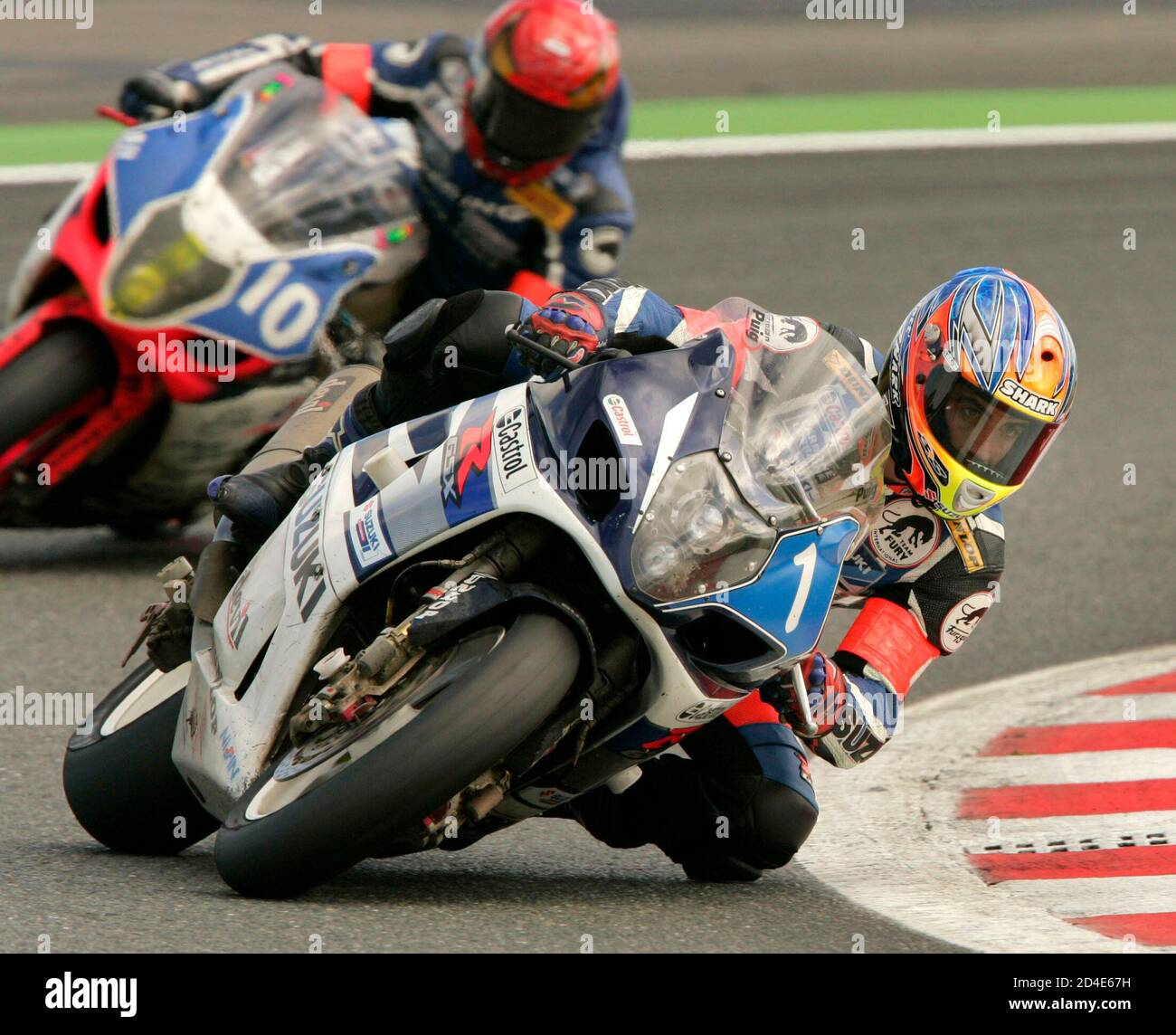 Matthieu Lagrive of France drives his Suzuki GSXR 1000 to lead the Bol d'Or endurance motorcycling race after 22 hours of competition in Magny-Cours.  Suzuki Castrol Team rider Matthieu Lagrive (R) of France drives his Suzuki GSXR 1000 to lead the Bol d'Or endurance motorcycling race after 22 hours of competition in Magny-Cours, France September 12, 2004. Behind (L) is the Infini Team Moto Suzuki GSXR 1000 in seventh place. REUTERS/Robert Pratta Stock Photo