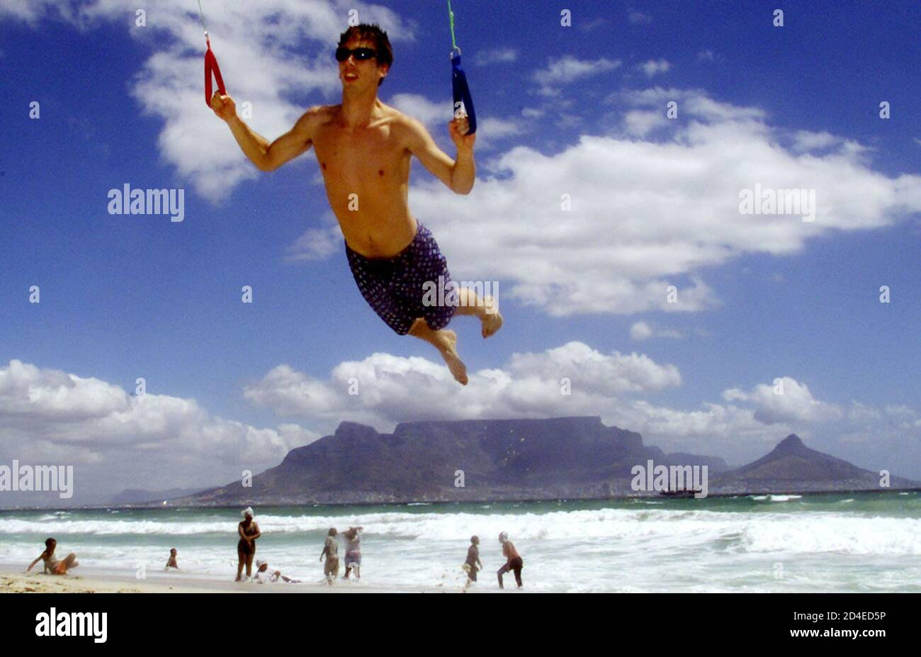 British tourist William Hayley-Borrell gets airbourne as he celebrates the New Year practising power-kiting moves on Blouberg beach near Cape Town, January 1, 2002. Drawn by the warm southern hemishere summer weather and spectacular backdrops, as well as a favourable exchange rate following the sharp fall in the Rand, it is estimated that about three million visitors will visit the city over the holiday period. REUTERS BOOKS The Art of Sport REUTERS/Mike Hutchings  MH/WS Stock Photo