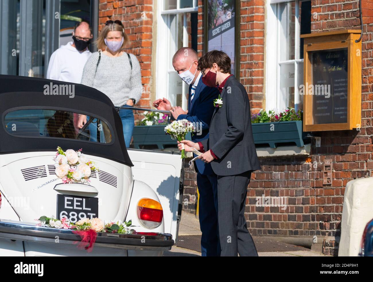 A couple wearing facemasks getting into a wedding car at a COVID safe event during the COVID19 Coronavirus pandemic in West Sussex, England, UK. Stock Photo