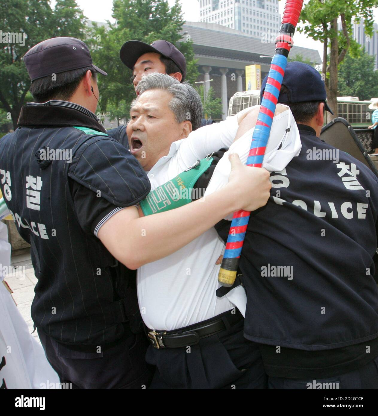 A South Korean anti-Japan protester, who tried to access the convoy of Japanese Prime Minister Junichiro Koizumi, is detained by police near the Presidential Blue House in Seoul June 20, 2005. Koizumi arrived in Seoul on Monday for a meeting with South Korean President Roh Moo-hyun to try to patch up ties frayed by disputes over their countries' bitter history. REUTERS/You Sung-Ho  KKH/CCK Stock Photo