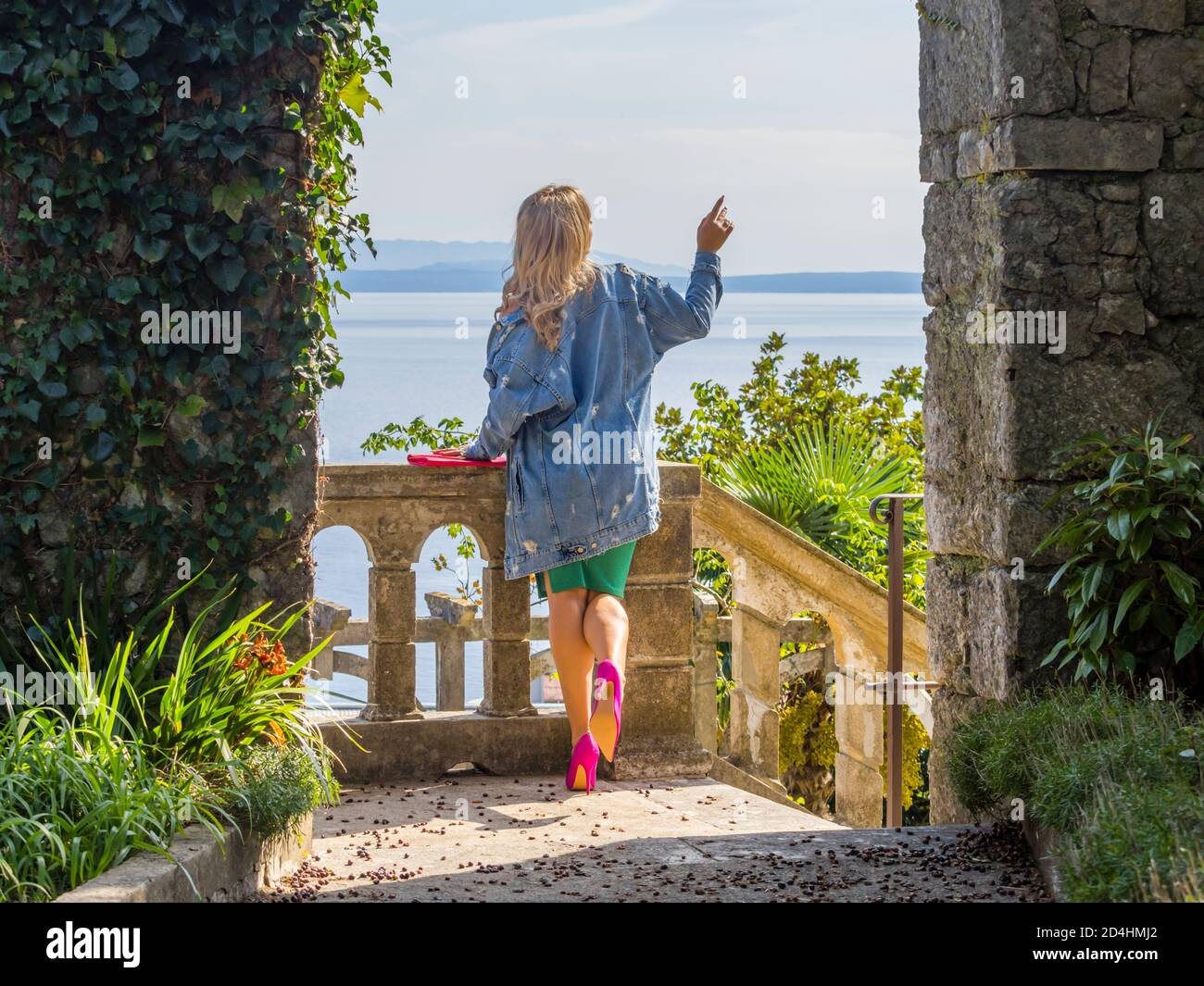 Blond young woman standing on balcony terrace promenade view from rear rearview behind aft legs Pink heels lifted raised raising leg showing something Stock Photo
