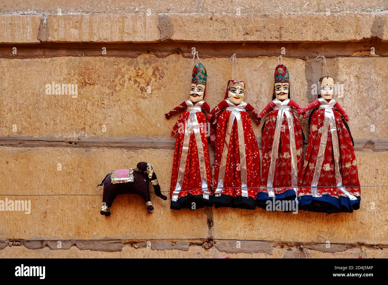 Colorful human shaped Puppets wearing colorful clothes hanging against the wall in Rajasthan India on 21 February 2018 Stock Photo