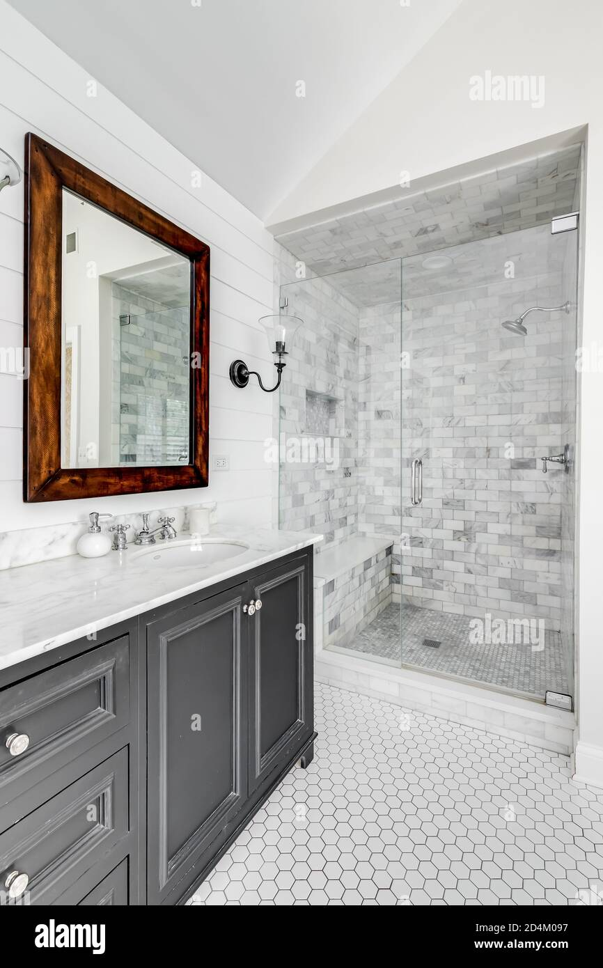 A luxurious renovated bathroom with a grey vanity, rustic wood framed mirror, and a stand up shower with a glass door and custom marble tile. Stock Photo