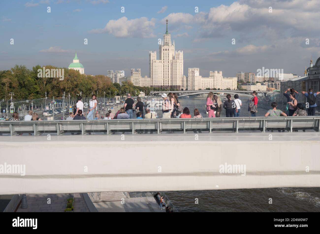 Tourists on the River Overlook, 70-metres long concrete console in Zaryadye park in central Moscow, Russia, against one of Seven Sisters skyscrapers Stock Photo
