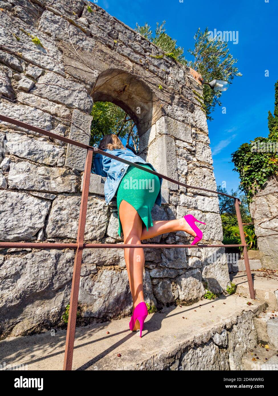 Pink high heels legs low view from rear rearview behind aft crop cropped lower waistdown body young woman looking through window opening of old house Stock Photo