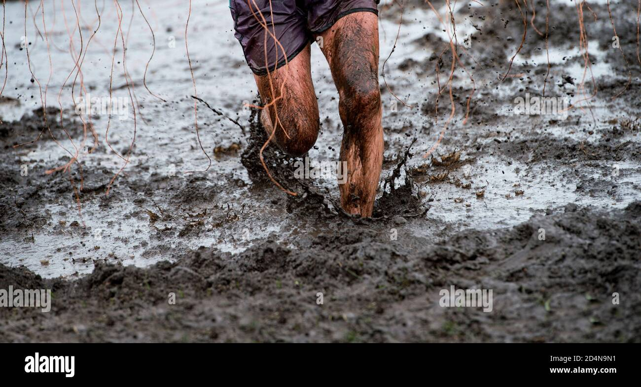 Mud race runner, man running in mud. Runners during extreme obstacle races. Active life and sport concept Stock Photo