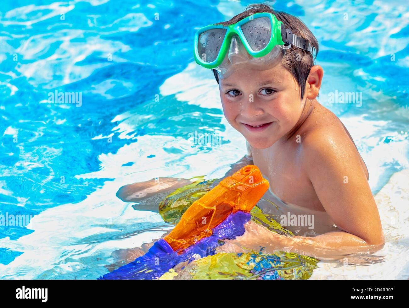 Smiling young boy with pool toys plays in a in ground pool Stock Photo