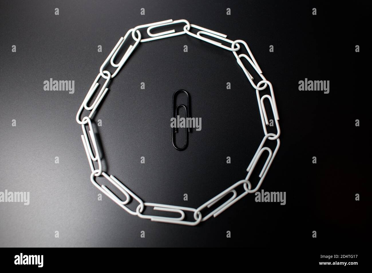 A circle of paperclips with one in the middle that is not fitting in and is surrounded. Symbolic representation of not fitting in the group and being Stock Photo