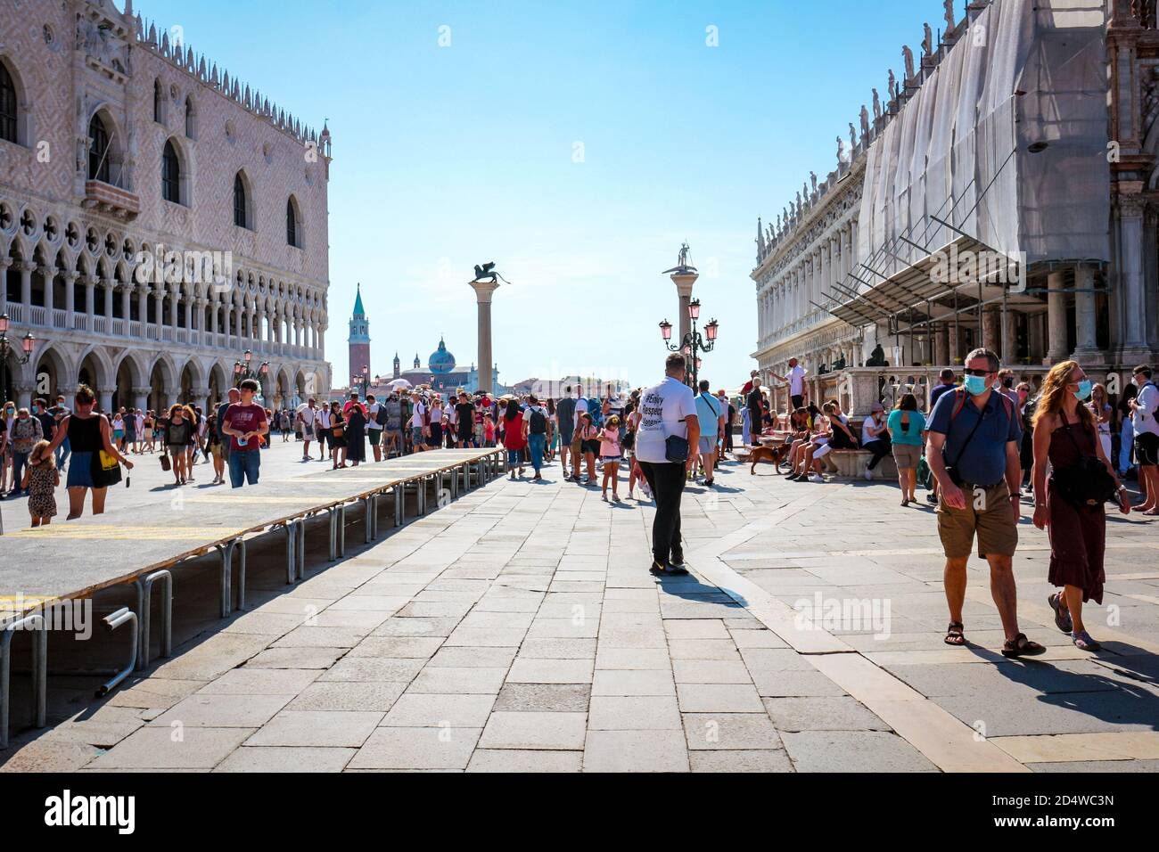 New normal tourism at Piazza San Marco (St. Mark's Square), Venice, Italy, during the coronavirus pandemic with tourists wearing face masks. Stock Photo