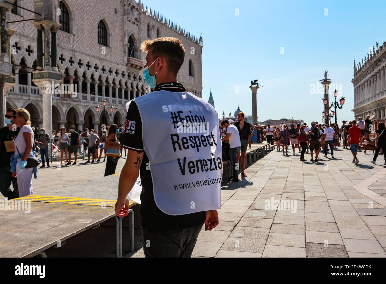 """""""#Enjoy Respect Venezia"""" guard in surgical face mask represents responsible tourism at St Mark's Square during the coronavirus crisis. Stock Photo"""