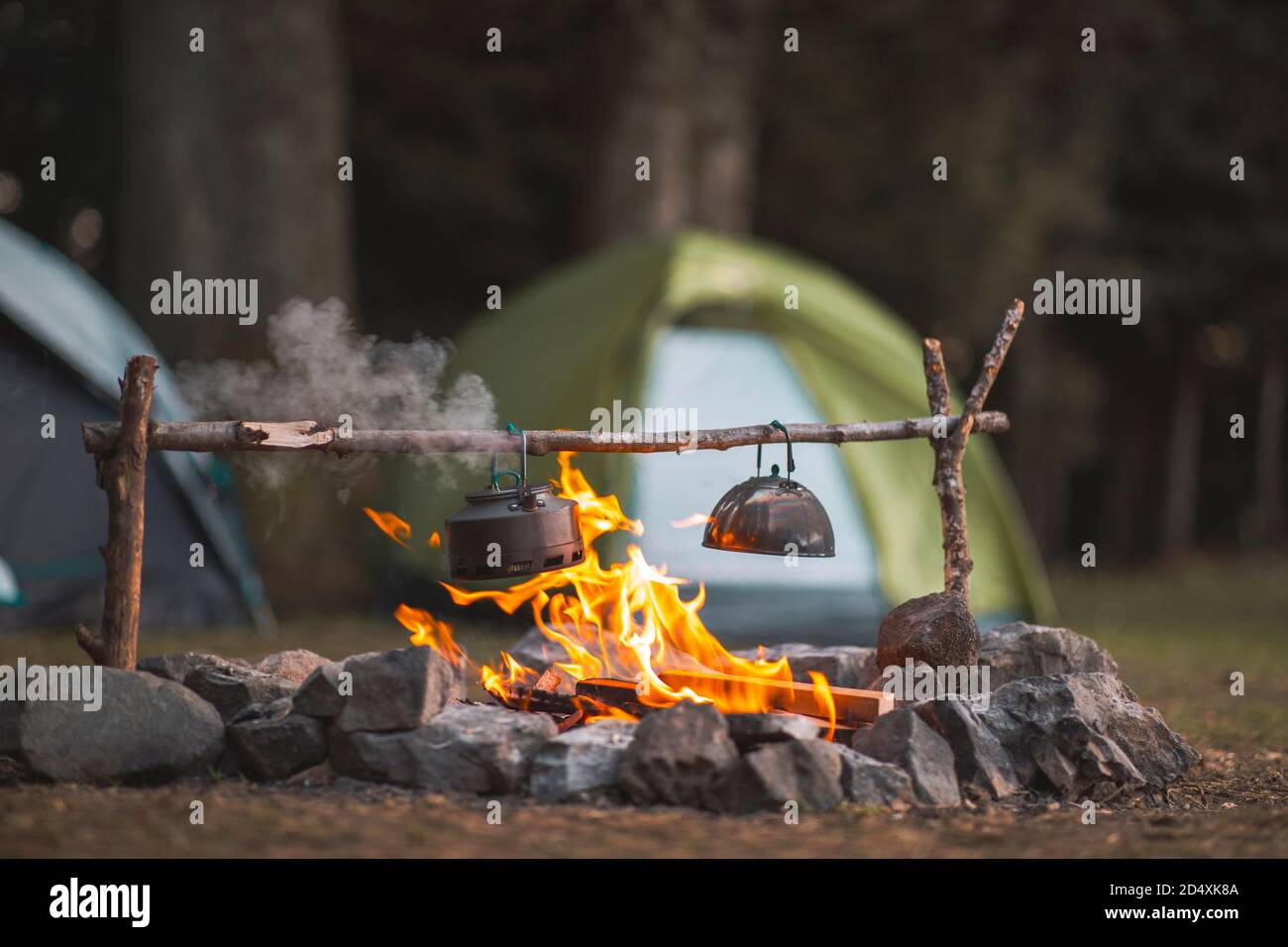 Camp fire and tea pot are foreground and focused, there is a tent in the background and defocused Stock Photo