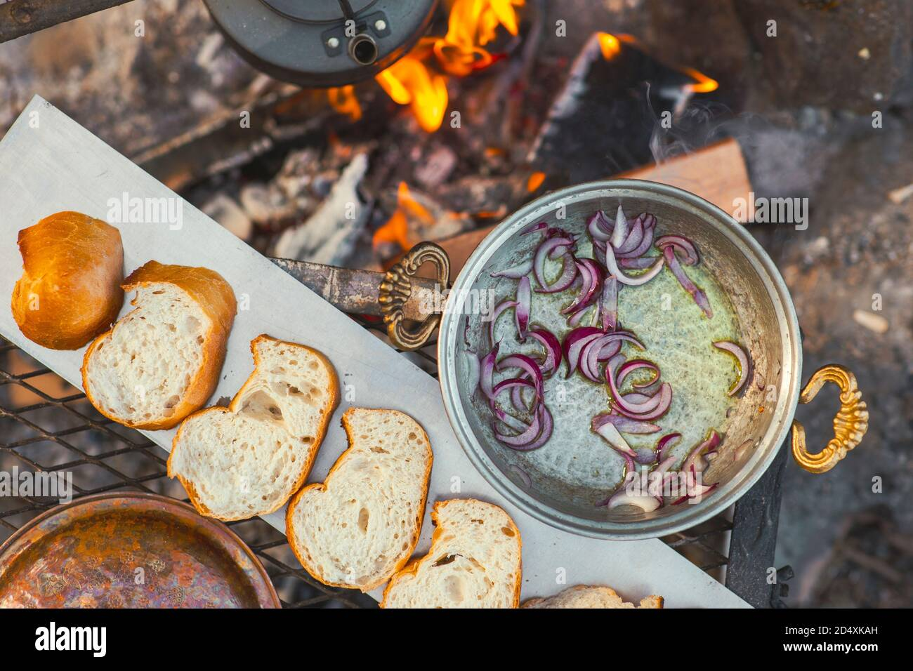 Flat lay view of camp fire cooking, breads are in a row, a tea pot and onion pan is on the fire Stock Photo