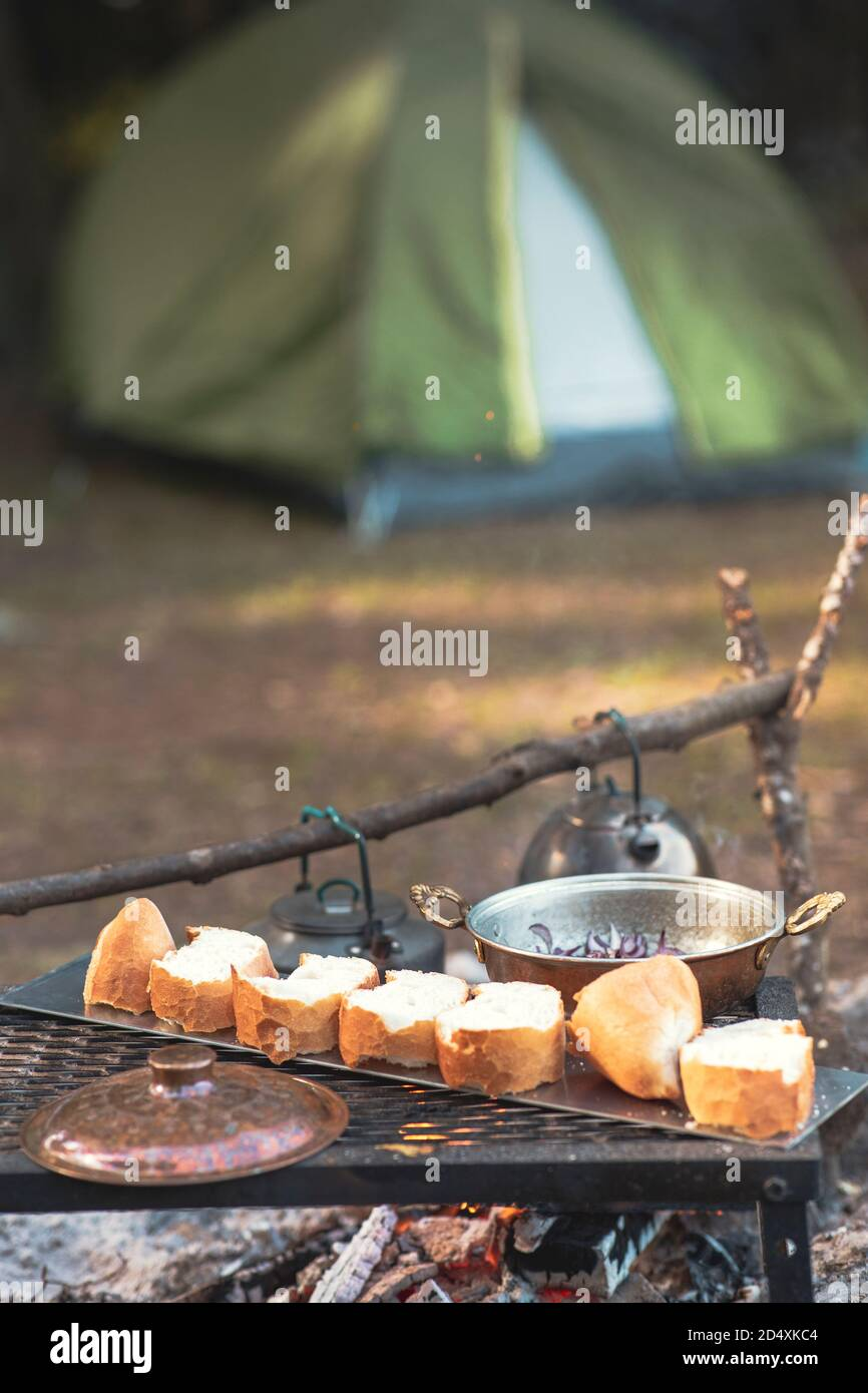 Camp fire and cooking pan are in foreground and focused, there is a tent in the background and defocused Stock Photo