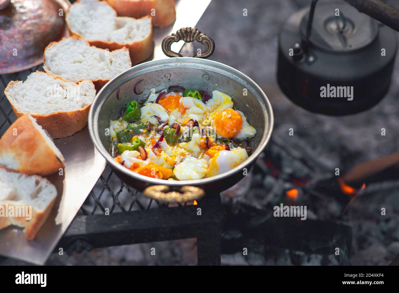 Detail view of camp fire cooking, breads are in a row, a tea pot and egg pan is on the fire with copy space Stock Photo
