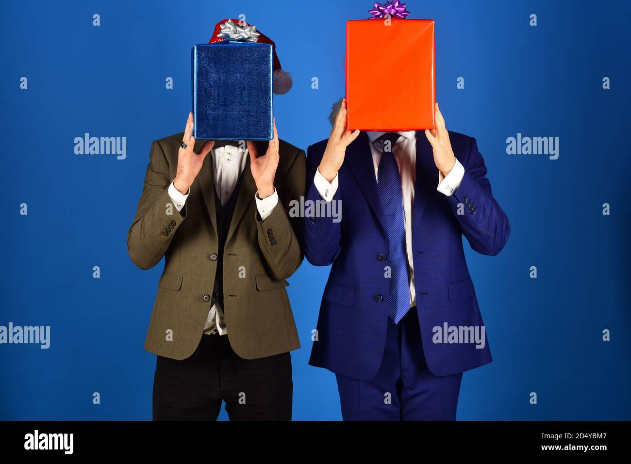Businessmen Hide Faces Behind Red And Blue Present Boxes Managers And Christmas Gifts Men In Smart Suits And Santa Hats On Blue Background Christmas Shopping Concept Stock Photo Alamy