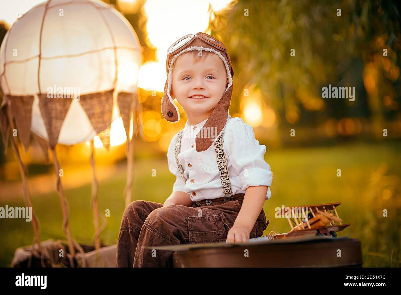 A little boy dreams of becoming a pilot. Vintage aviation hat. Stock Photo