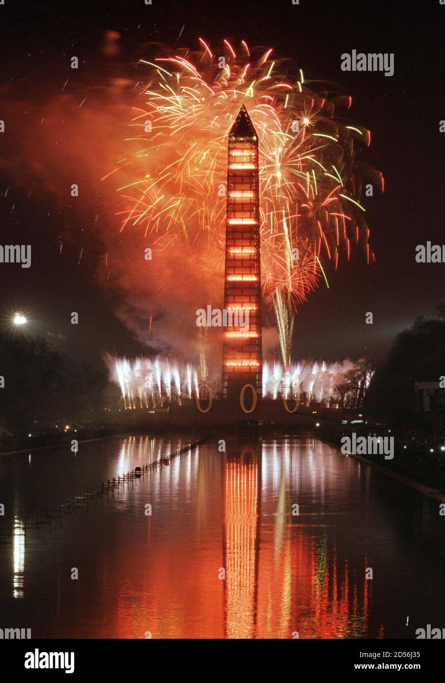 Fireworks explode above the Washington Monument in front of the reflecting pool as hundreds of thousands of spectators watch during the millennium celebration in Washington January 1. [Washington ushered in 2000 with rap, rock, a Steven Spielberg film, fireworks by the Washington Monument and -- for a hardy few -- a midnight wade in the reflecting pool.  ]   ??» Stock Photo