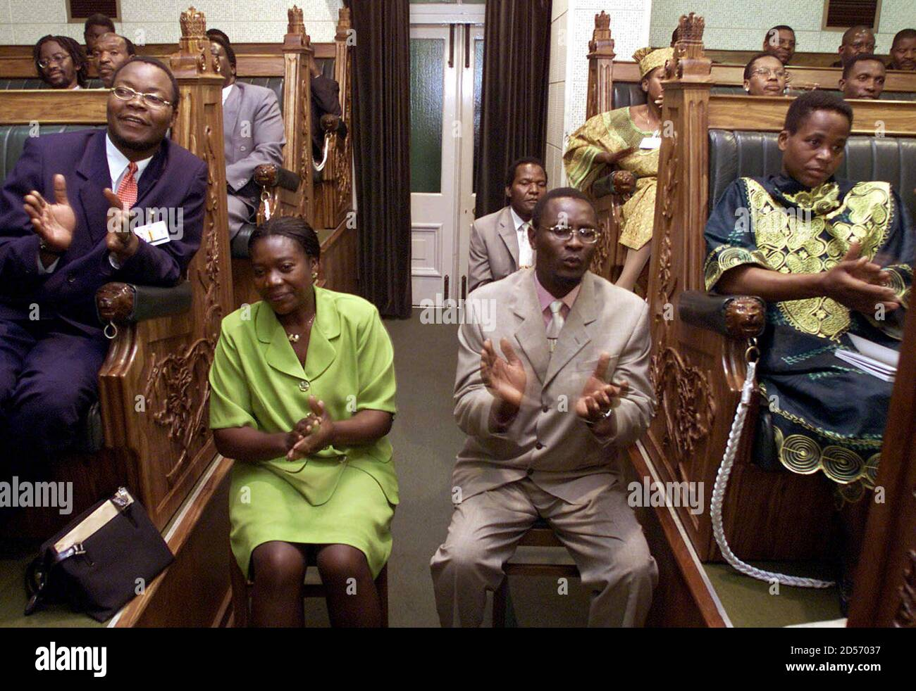 Movement for Democratic Change (MDC) members of parliament Hilda Mafudze (2L) and Gabriel Chaibva (2R), seated in the aisle of the backbenches, celebrate as a colleague takes their oath in Harare July 18. The MDC won 57 of 120 elected seats in the new parliament to give the ruling [ZANU (PF)] its first real opposition since independence in 1980. Stock Photo