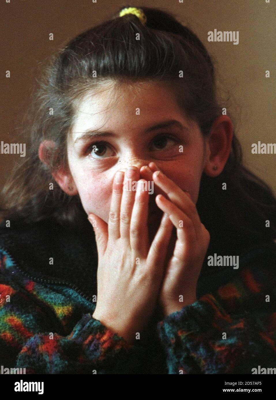 Besa Musliu, 9, an ethnic Albanian schoolgirl from the village of Racak holds her face as she stays indoors at the sound of mortar shelling January 19. Two ethnic Albanian families took shelter in a house in Petrovo after fleeing their village of Racak during shelling from Serb forces January 19. In Racak 45 civilians were found dead and villagers believe they were killed by Serbs last Friday January 16. Serbian police forces and Yugoslav army have been deployed around Racak village, about 26 km (16 miles) south of the regional capital Pristina and had been involved in an exchange of fire with Stock Photo