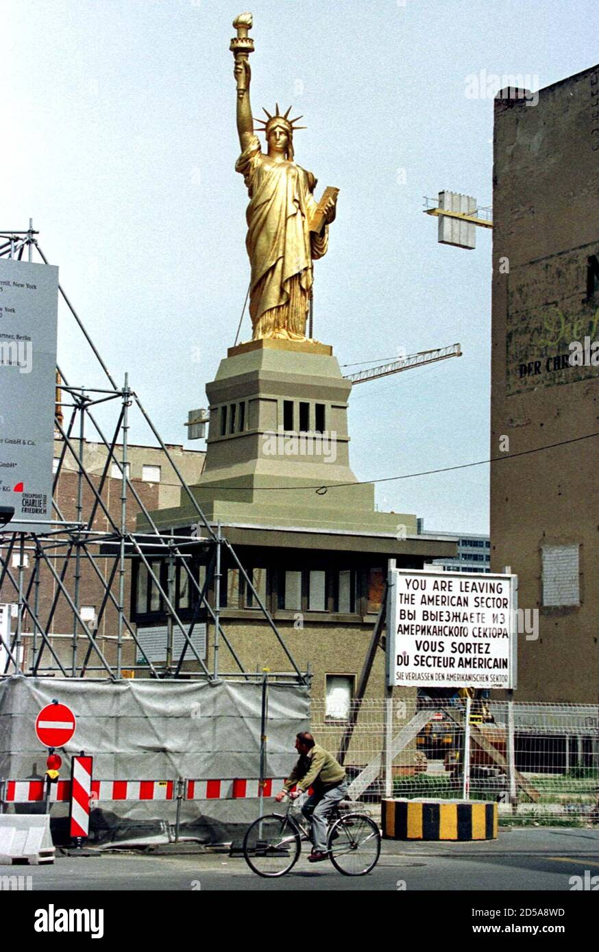 """A cyclist passes a giant copy of the """"Statue of Liberty """", May 29 which has been set up on top of a former east-German border guard watchtower at the former allied Checkpoint Charlie which is now a large construction site where U.S. investors build the American trade center. The sign reads in English, Russian, French and German """" You are leaving the American sector Stock Photo"""