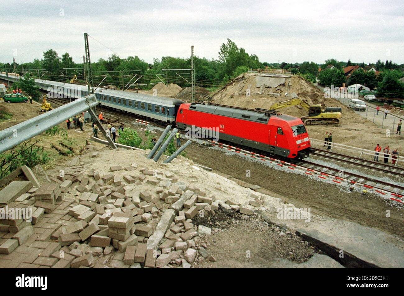 Rail traffic resumes with the first commuter train slowly passing by the crash site in Eschede June 9, where a German InterCity Express high-speed train, travelling at 200 kmh (125 mph), derailed and slammed into a road bridge June 3, leaving some 100 people dead and nearly 50 seriously injured. German railway Deutsche Bahn AG said the cause may have partly been due to a damaged wheel and withdrew sixty of the first generation ICE trains from service for special safety checks including an ultrasound test of the wheels.  CHA/EB Stock Photo