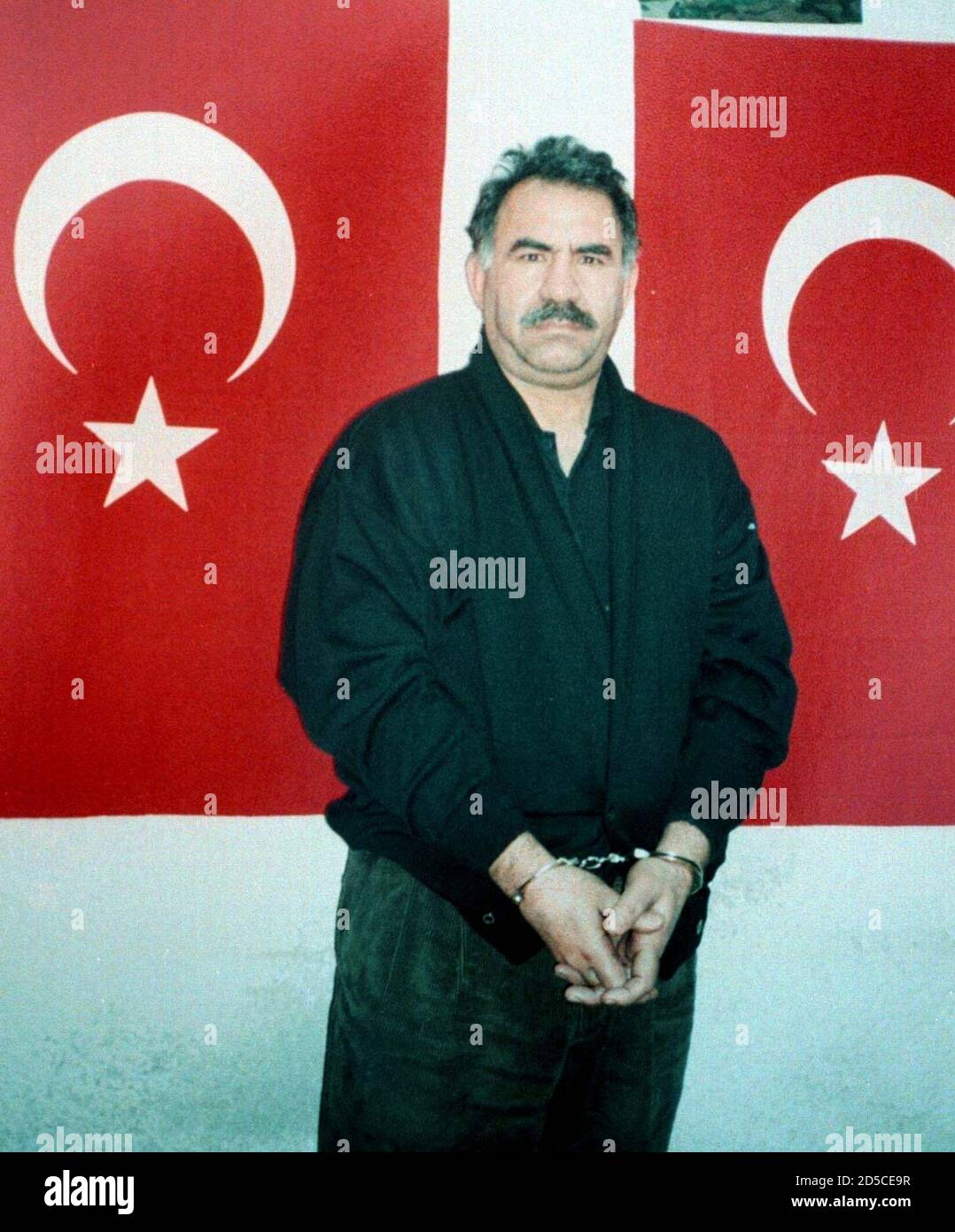 Kurdish rebel leader Abdullah Ocalan poses for the camera between two Turkish flags after he arrives on an island prison of Imrali, in the Sea of Marmara some 60 kms (37 miles)
