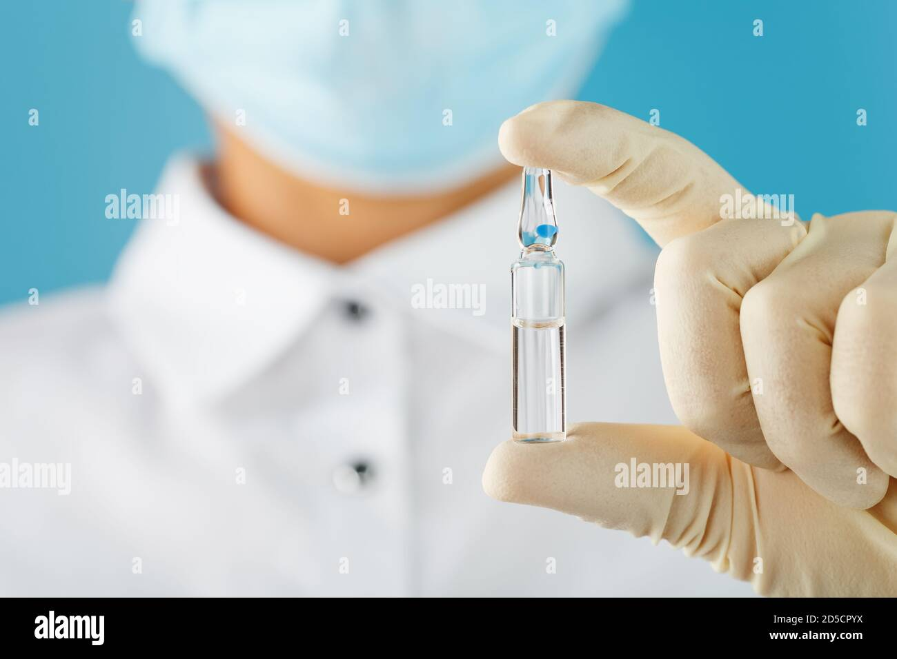 In the hands of a research scientist, a doctor in rubber gloves, an ampoule with a vaccine close-up. Stock Photo