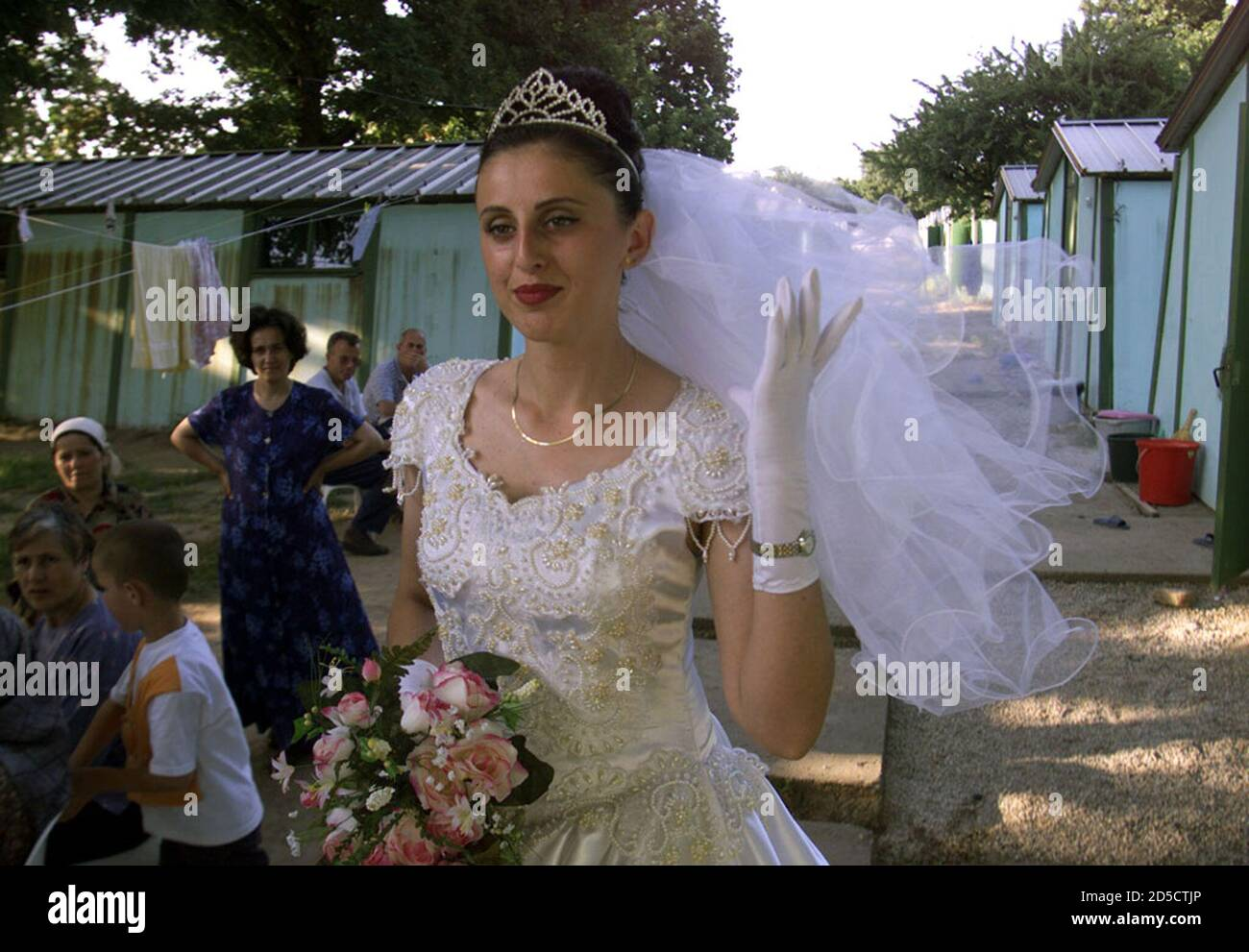 An Albanian Kosovar refugee bride Besa Karabek adjusts her bridal veil as she is admired by neighbouring refugees late June 13 waiting for her wedding among the huts at a refugee camp in western Turkey where nearly 7,600 Kosovar refugees took shelter since they fled Kosovo. Twenty-year-old Kosovar refugee Besa Karabek is the first bride in this refugee camp near the western Turkish city of Kirklareli, 200 kms from Istanbul.  FS/WS Stock Photo