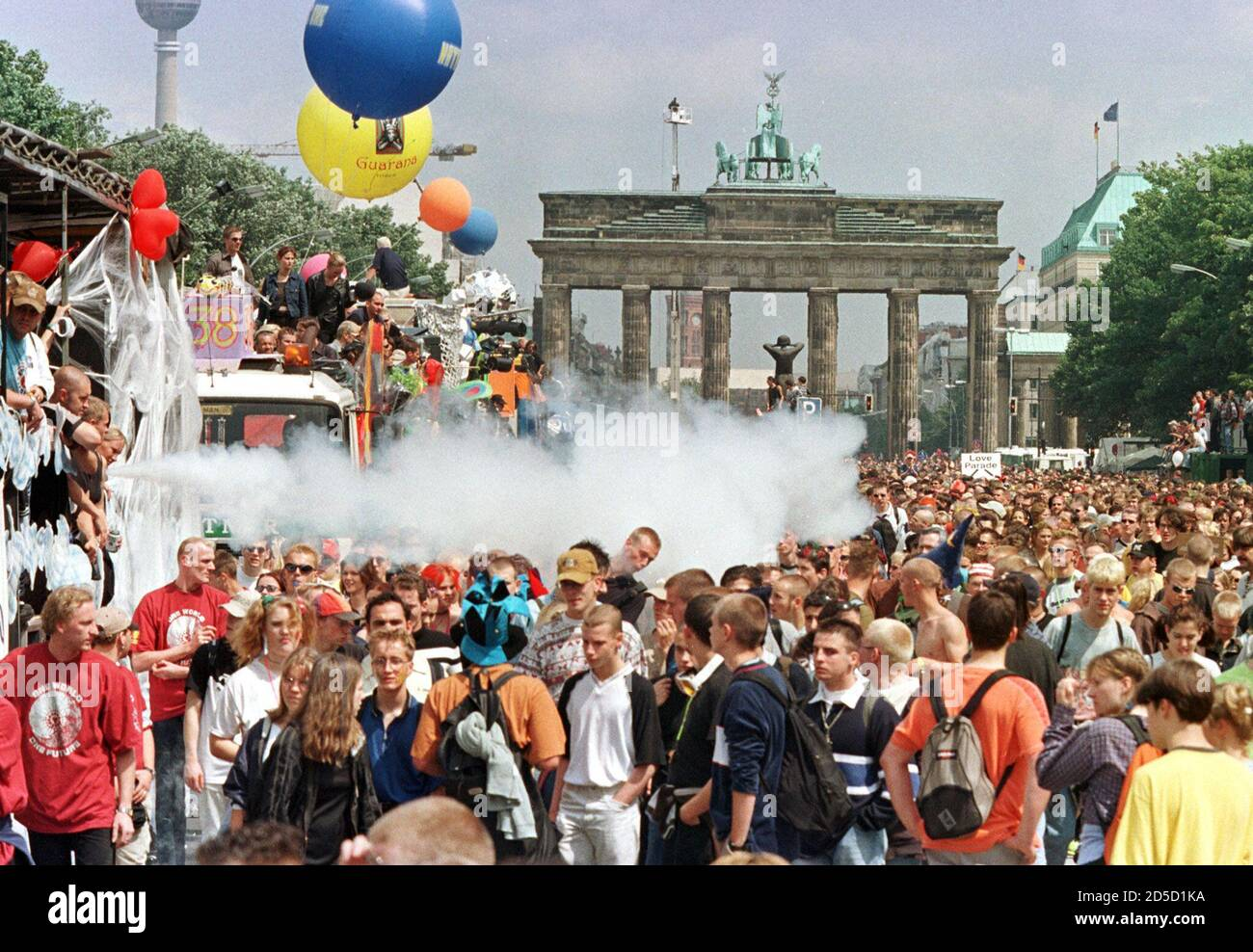"""Revellers at Berlin's famous landmark, the Brandenburg Gate, watch floats make their way through the dense masses during the German capital's annual """"Love Parade"""" techno music fest July 11. Over a million people are expected to attend this year's tenth anniversary street parade with the motto """"One World, One Future"""". Stock Photo"""