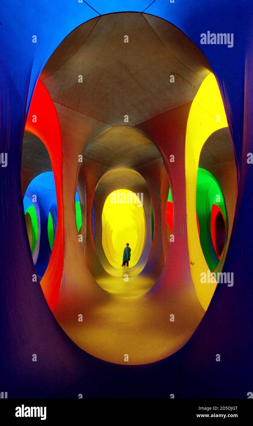 An artists assistant examines the inflatable interactive sculpture entitled 'Dreamspace' on Shepherd's Bush Green in London, July 25.  The large inflatable network of coloured tunnels was created by artist Maurice Agis, and participants are encouraged to wear coloured overalls as they wander through the structure to the accompaniment of ambient music. Stock Photo