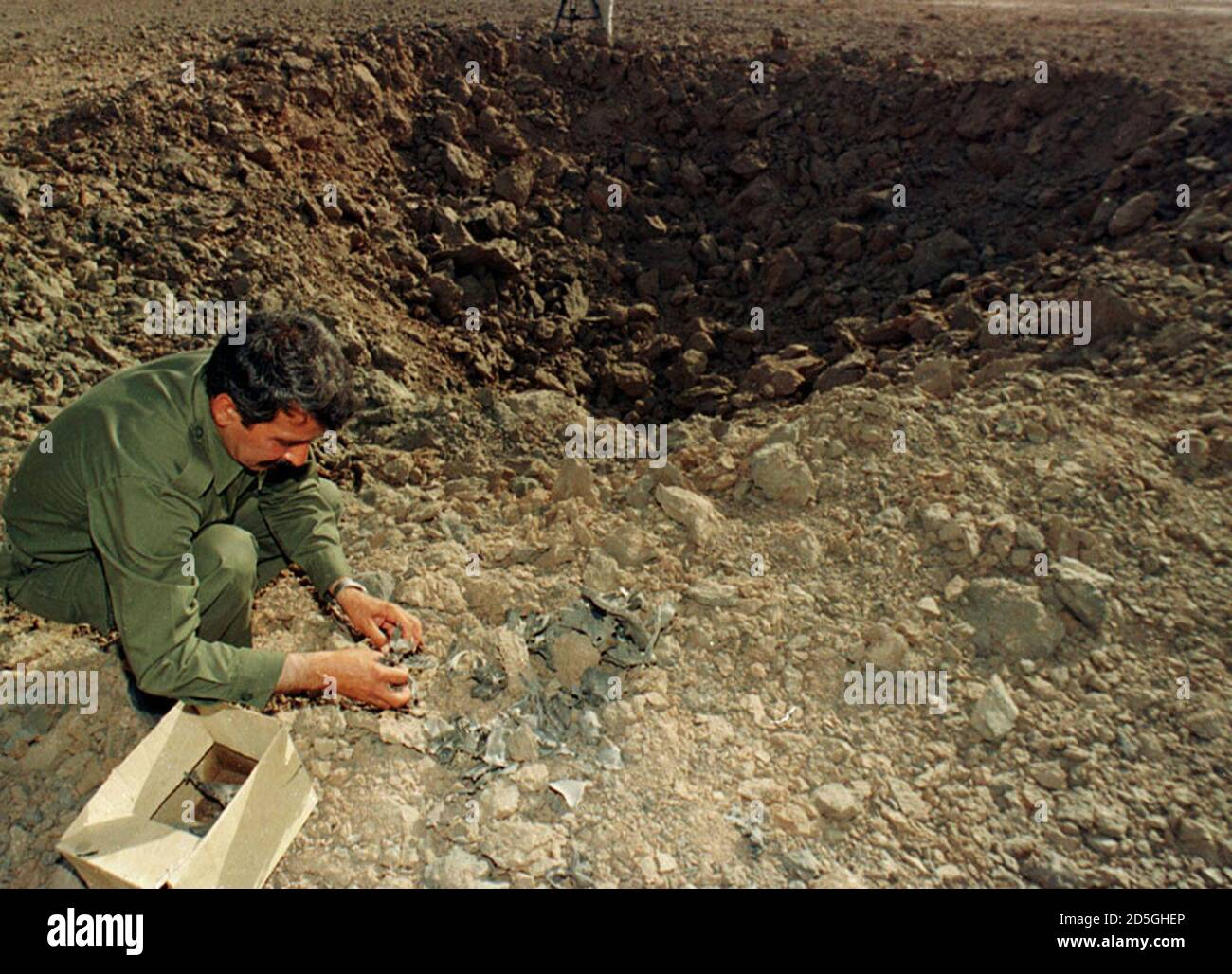 A Mujahideen fighter collects pieces of an Iranian missile June 11 which attacked a Mujahideen camp at Ashraf yesterday. Iraq said on Friday that Iran had fired three long-range misiles at an Iranian exile opposition group based inside Iraq. The official Iraqi news agency said that the camp belonged to Iranian opposition group Mujahideen Khalq. Ashraf is 100kms northeast of Bahgdad.  FK/KM Stock Photo