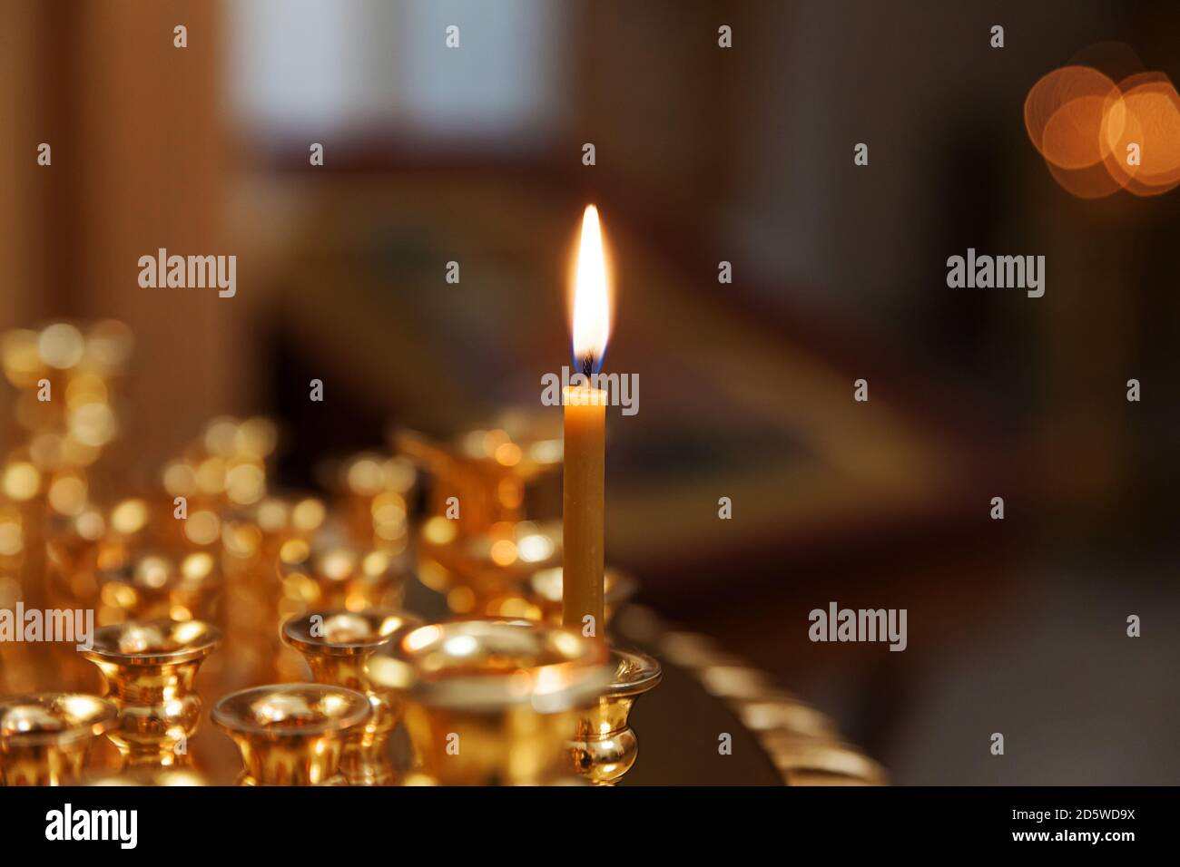 Orthodox Church. Christianity. Festive interior decoration with burning candles and icon in traditional Orthodox Church on Easter Eve or Christmas. Religion faith pray symbol Stock Photo