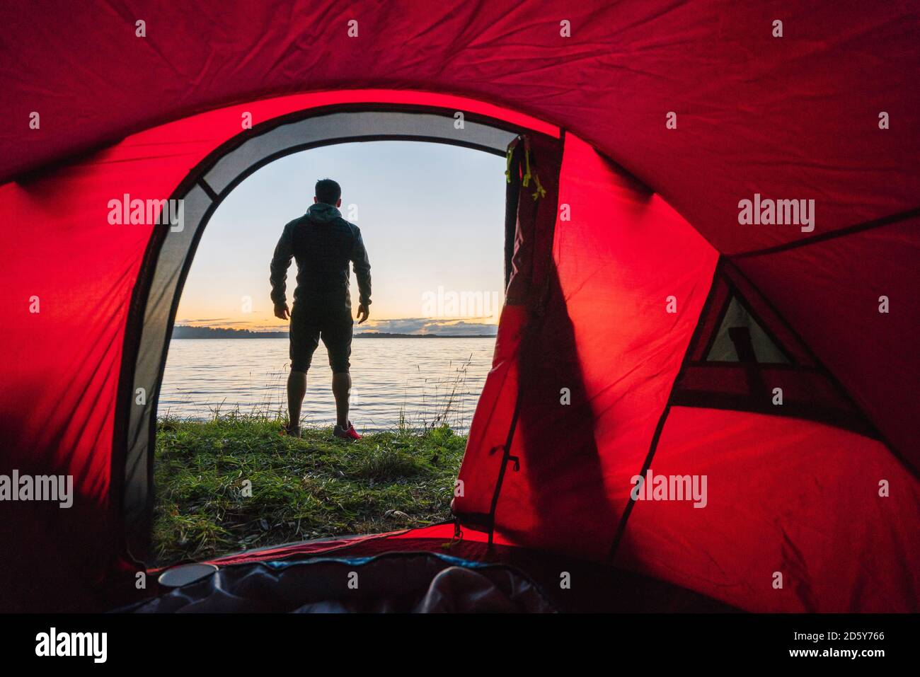 Man camping in Estonia, standing in front of tent, watching sunset Stock Photo