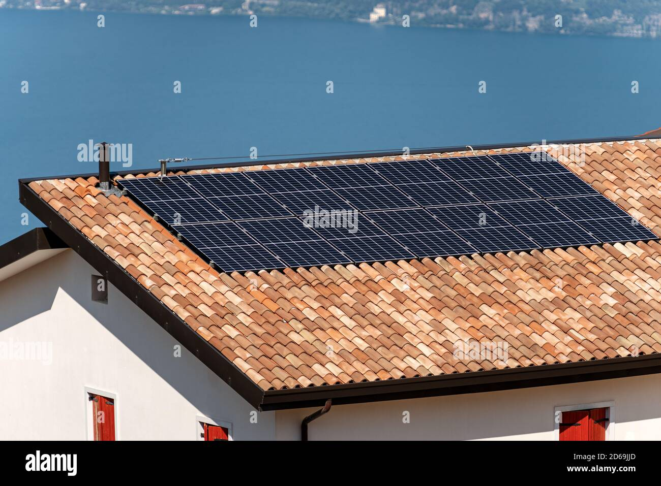 Solar panels on the roof of a house with a blue lake on the background. Renewable energy concept Stock Photo