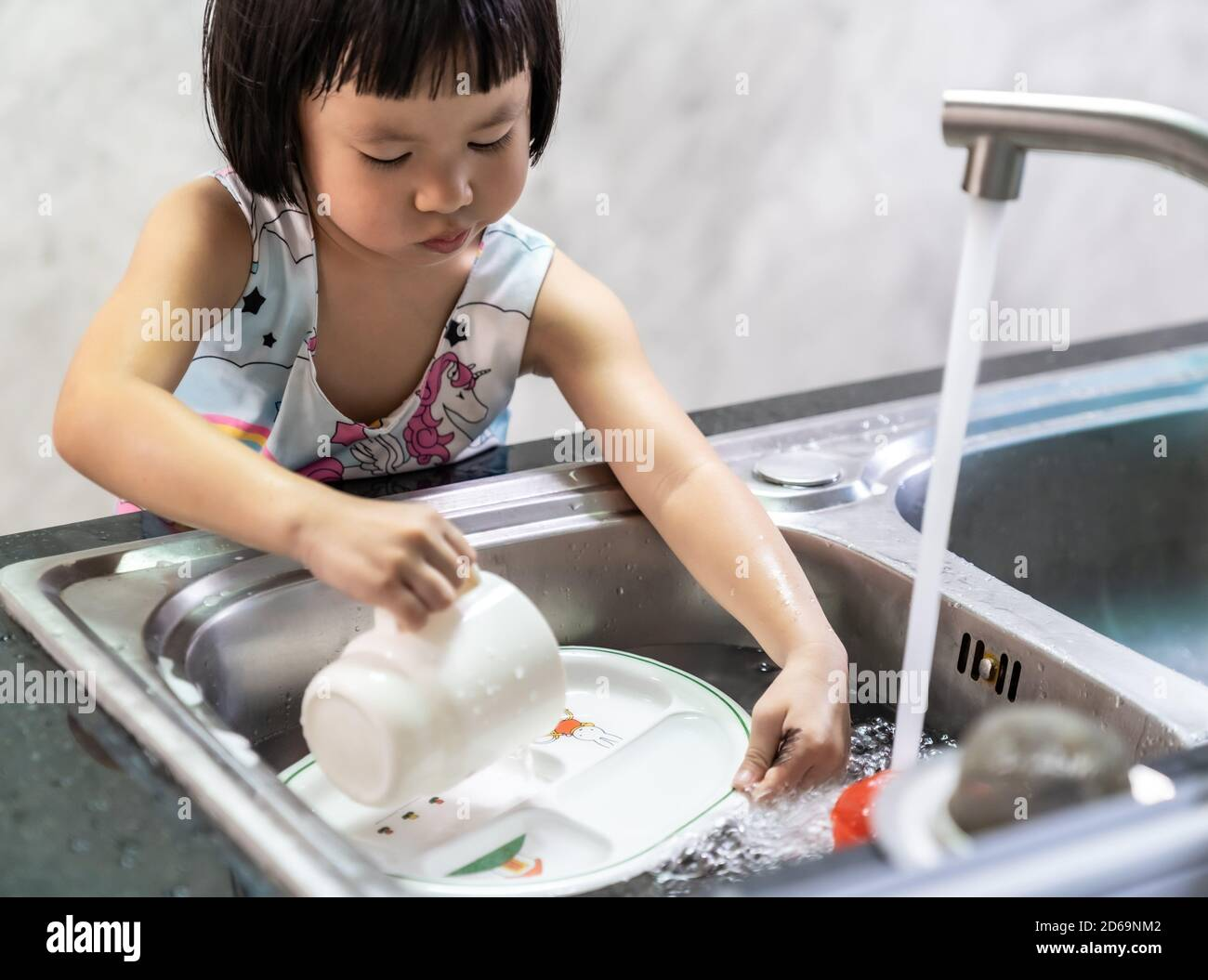 Asian girl washing her dish and tableware by herself, housework for child make executive function for kid. House-working for kid lifestyle and family Stock Photo