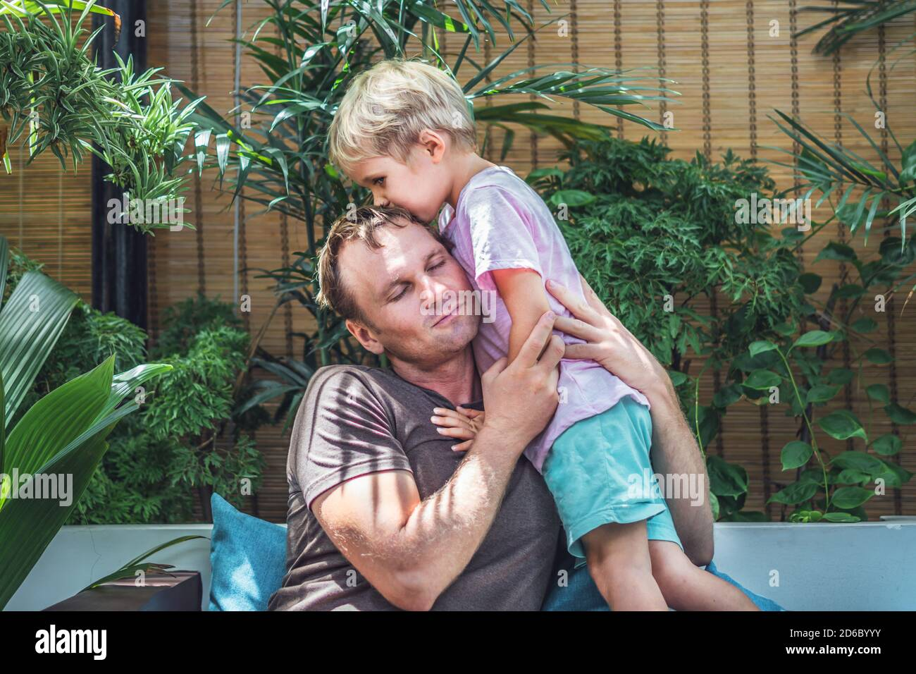 Father gently hugs son, eyes closed with pleasure, blond little child boy kiss daddy head top, face to face, bright sun light green leaves back. Happy Stock Photo