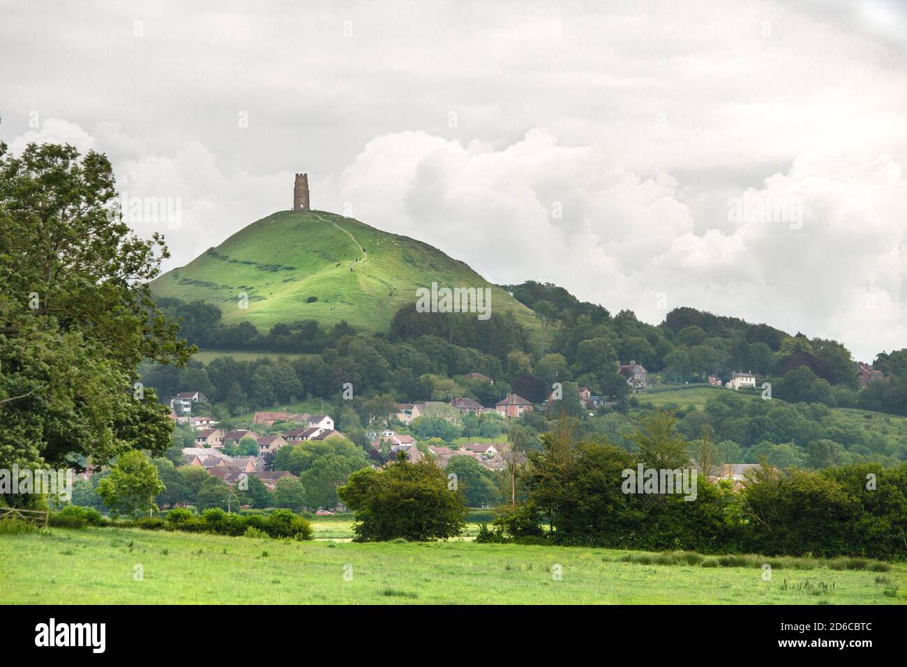 Fluffy white clouds frame Glastonbury Tor in the summer. Farmland frames the foreground, with the red roofs of Glastonbury town in the center valley. Stock Photo