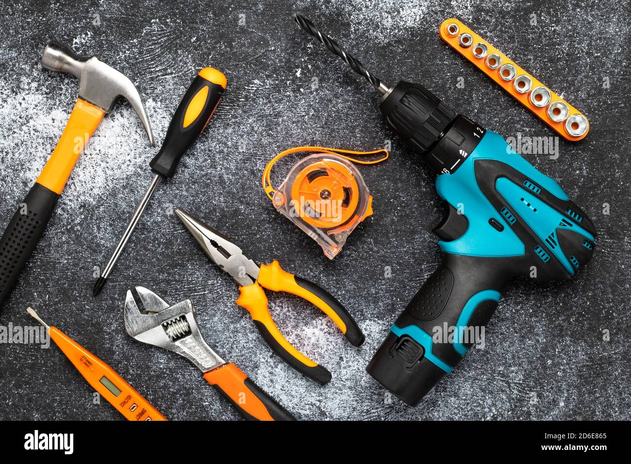 Set of tools on a dark background. Renovation concept, housework. Flat lay composition. Electric drill, screwdriver, tape measure, wrench, knife and h Stock Photo