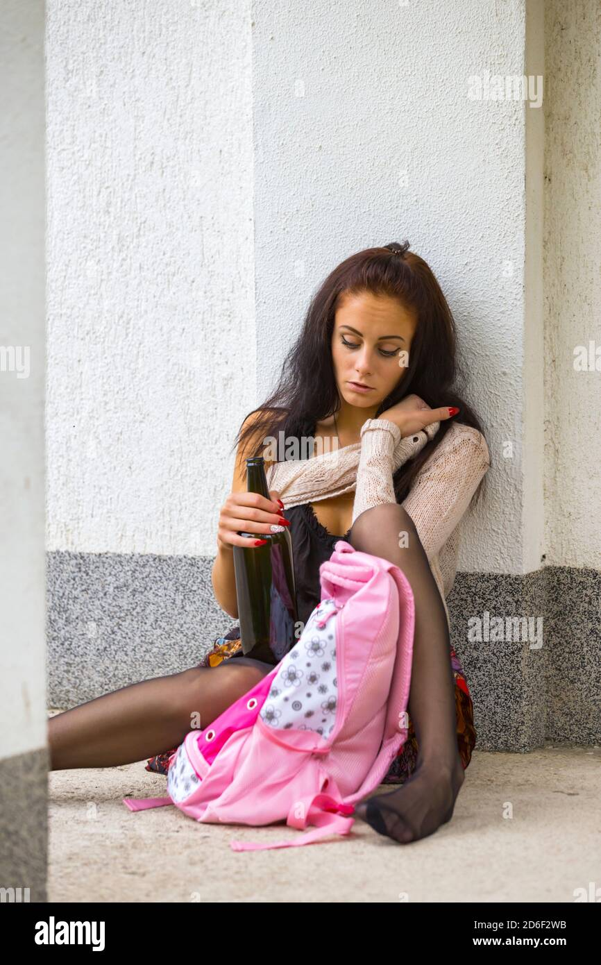 Schoolgirl school-girl teengirl hand holding hold bottle of alcohol alcoholic drinker sitting awkward barefeet looking down serious barefeet with bag Stock Photo