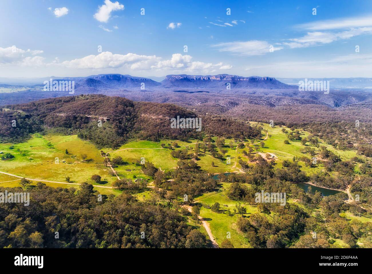 Capertee valley in aerial view above gumtree woods and green pastures between mountain ranges. Stock Photo