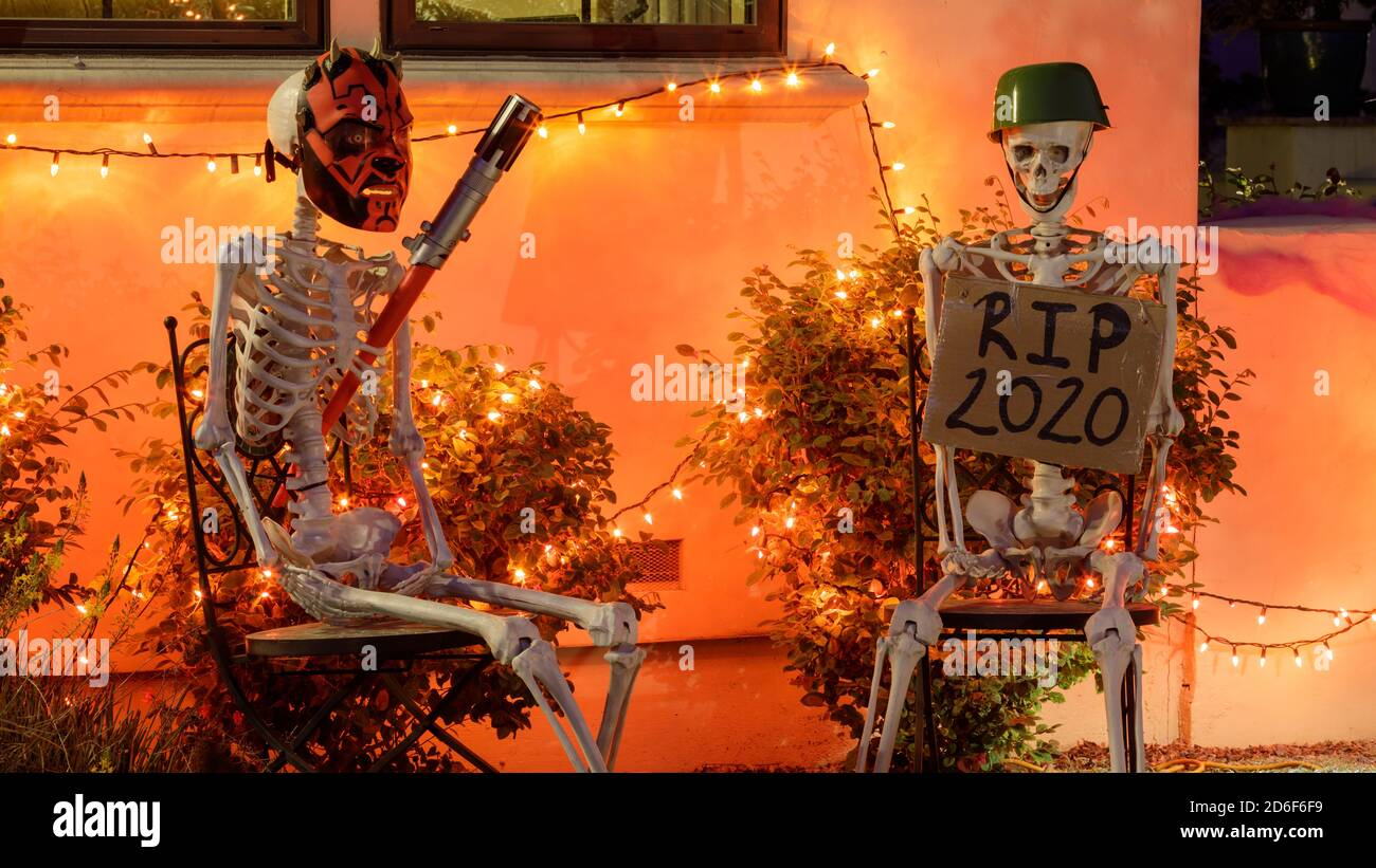 Two skeletons sitting on chairs outside a house for Halloween Stock Photo