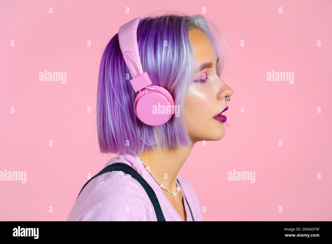 Close-up portrait of pretty girl with dyed violet hair listening to music, smiling, dancing in headphones in studio against pink background. Music Stock Photo