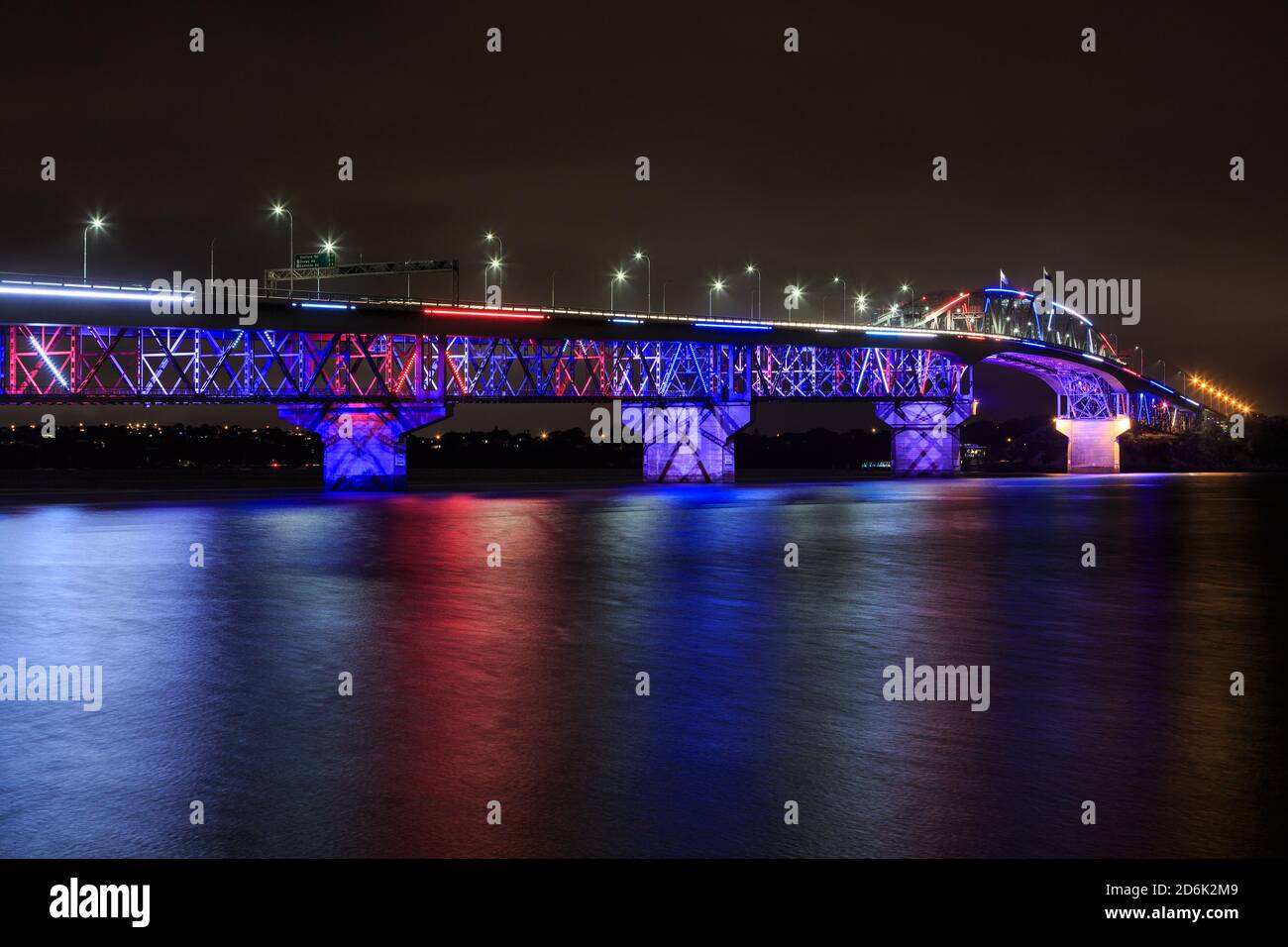 The Auckland Harbour Bridge, Auckland, New Zealand, colorfully lit up at night for Auckland Anniversary Stock Photo