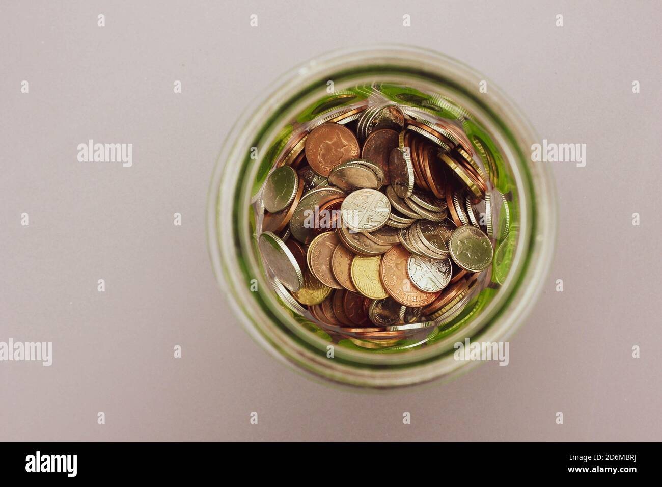 Money jar full of coins. Taken from above. Space for copy. Stock Photo